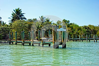 Old wooden pier with blank sign in tropics