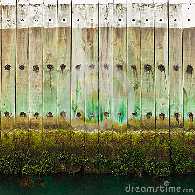 Old wooden pier wall with tidal waterline