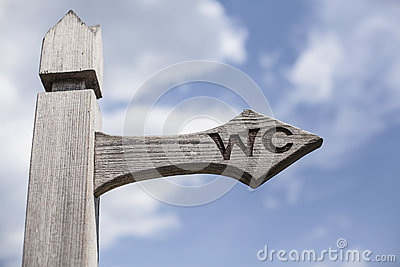 Old wooden signpost over blue sky.