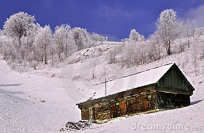 Old wooden stable with snow on the roof