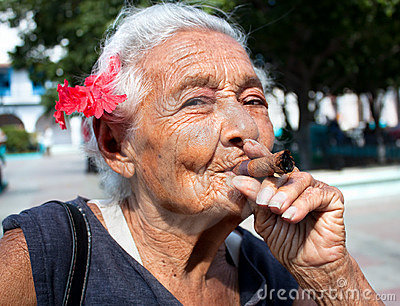 Old wrinkled woman with red flower smoking cigar