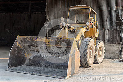 Old yellow tractor parks in factory