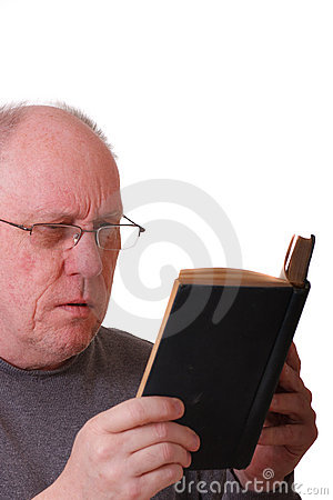 Older Balding Man Reading a Black Book or bible