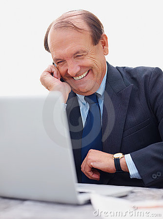 Older business man using laptop while on the phone