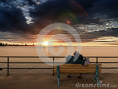 Older couple on bench enjoying Sunset