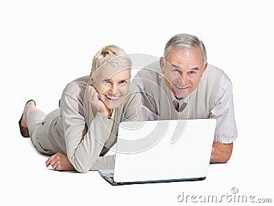 Older couple lying and using laptop on white