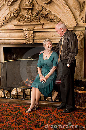 Older couple portrait by fireplace