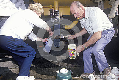 An older couple securing some water from a water Editorial Photography