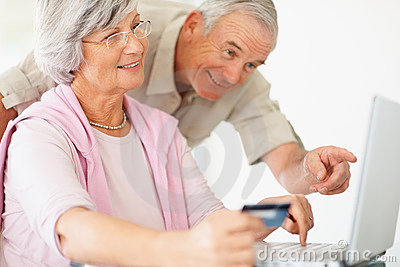 Older couple using a credit card to shop