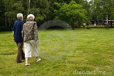Older couple walking through a park