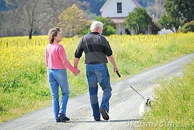 Older couple walking their dog on a country road