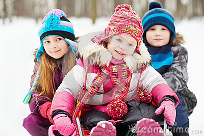 Older girl and boy push sled in which younger girl sits