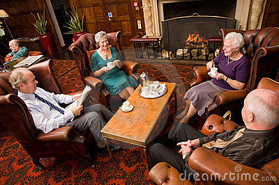 Older group of friends by fireplace