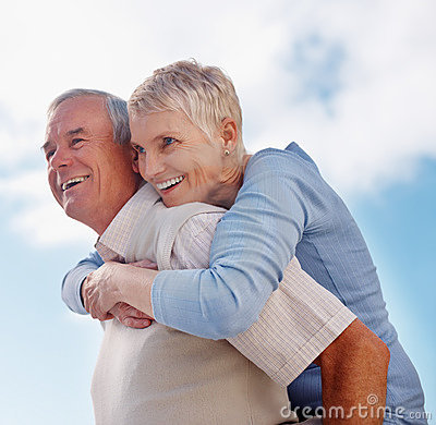 Older man giving woman piggyback ride to wife