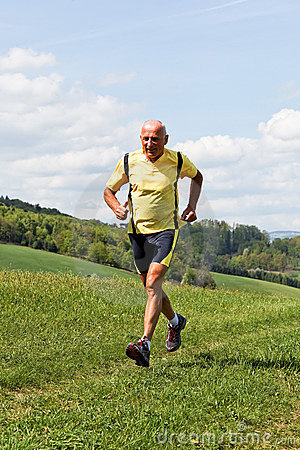 Older man jogging running on meadow