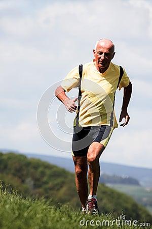 Older man jogging running on meadow