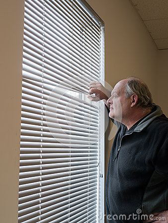 Older man looking out window blinds.