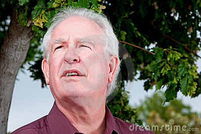 Older man looking skyward with concern