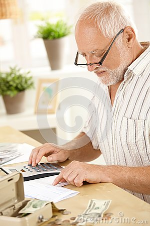 Older man using calculator at home
