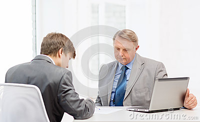 Older man and young man signing papers in office