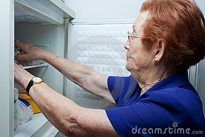 Older woman looking for food in the fridge