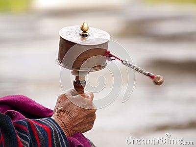 An older women spinning her prayer wheel
