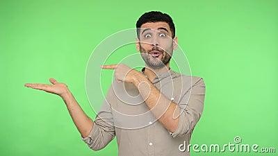 Olha aqui! Homem maravilhado extremamente feliz na camisa segurando palma e apontando espaço para cópia tiro de estúdio filme