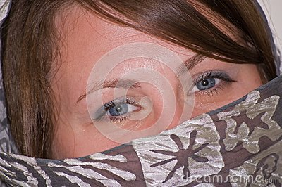 Olhos azuis do close up da jovem mulher com Gray Scarf