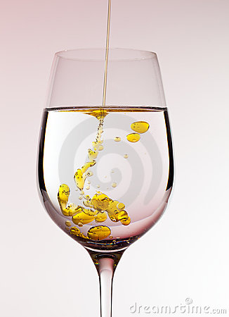 Olive oil being poured into wine glass
