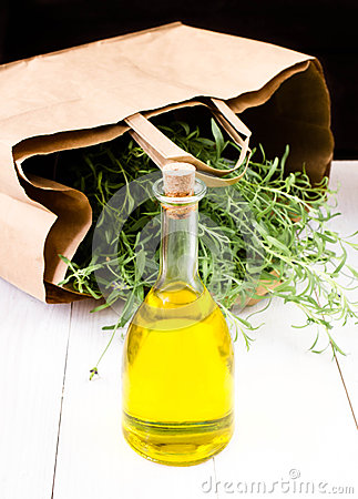 Olive oil bottle and herbs with Paper bag on white wooden  backg