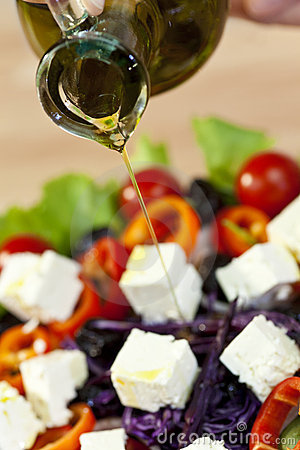 Olive Oil Dressing Pouring Onto Fresh Salad