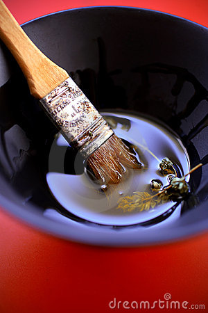 Olive oil with herbs in black bowl with brush