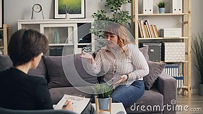 Olycklig överviktig dam som upp till öppnar psykologen i modernt kontor lager videofilmer
