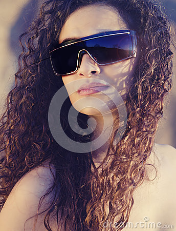 Oman with gorgeous curly hair wearing sunglasses