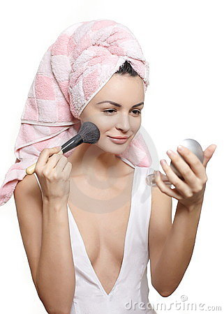 Oman in towel on the head applying makeup