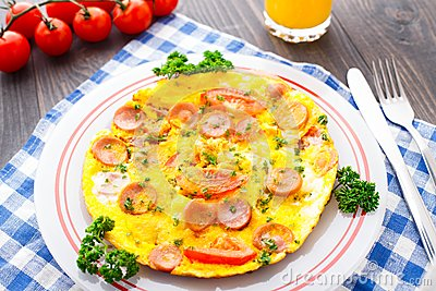 Omelette with slices of sausage and tomato