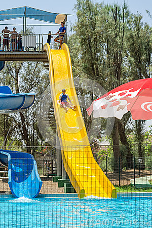 Free Omer, ISRAEL - July 25, 2015 In Israel Children Walk Down The Yellow Water Slides In The Outdoor Pool Royalty Free Stock Image - 57130546
