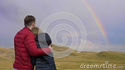 Omhelst jongen en meisjespaar van minnaars die het mooie landschap met heuvels en regenboog bewonderen - stock video