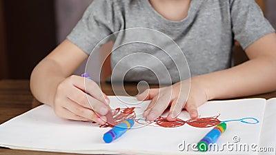 Onbekende kindtekening met heldere kleurpotloden op Witboek terwijl het zitten bij de lijst Het concept ontwikkeling stock video