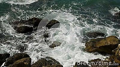 Ondas con la espuma del mar en el golpeo de Montenegro en las rocas cubiertas almacen de metraje de vídeo