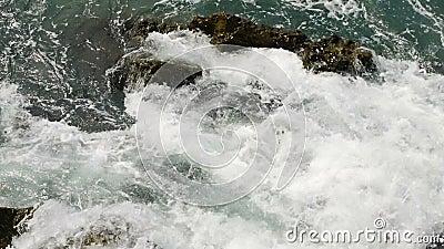 Ondas con la espuma del mar en el golpeo de Montenegro en las rocas cubiertas metrajes