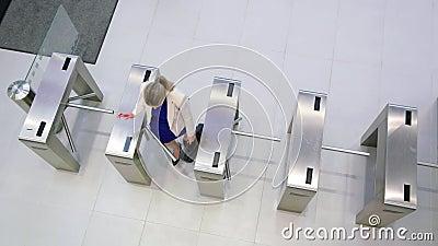 Onderneemsters die hun kaarten aftasten bij turnstile poort stock footage