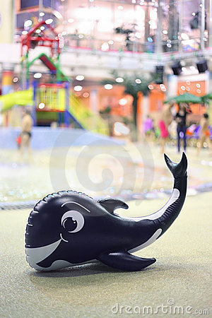 One amusing inflatable whale lies near pool