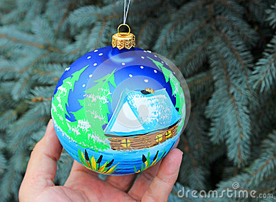 One blue christmas ball handing on a tree.