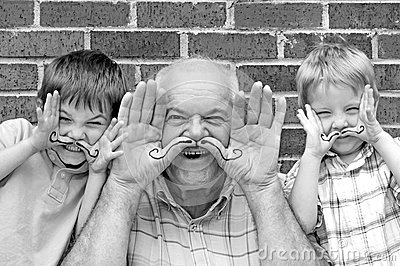 Grandpa and grandsons playing with hand moustaches
