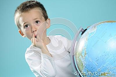 One child evaluating destinations on globe
