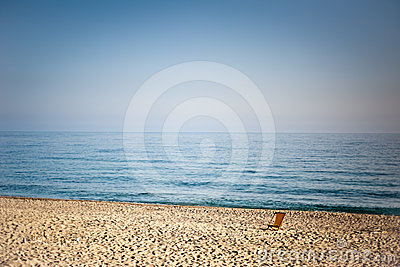 One empty chaise longue on the beach