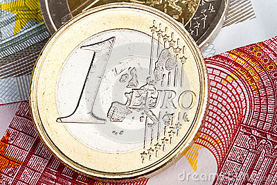 One Euro coin over banknotes
