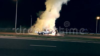 One firefighter dousing the burning vehicle with foam at the scene of the car crash stock video