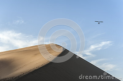 One glider plane fly over the sand dunes